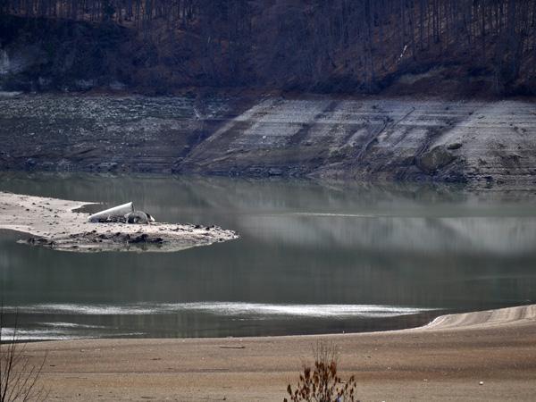 Basses eaux au lac de la Gruyère, 3 avril 2011. L'île d'Ogoz devient un but de promenade dominicale pour toute la famille et le lac se mue en un étrange désert...
